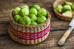 Fresh Brussels Sprouts. Many Fresh Green Brussels Sprouts in a Basket on Wooden Background Stock Photography