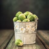 Fresh Brussels sprouts in metal bucket. On old wooden table. Healthy food concept with copy space. Retro style toned Royalty Free Stock Photography
