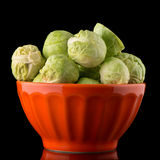Fresh brussels sprouts. On orange ceramic bowl isolated on black background Stock Images