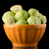 Fresh brussels sprouts. On orange ceramic bowl isolated on white background Stock Photos