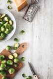 Fresh Brussels Sprouts with Parmesan Cheese for Cooking. On wooden Background royalty free stock photo