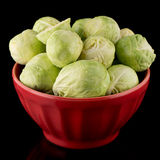 Fresh brussels sprouts. On red ceramic bowl isolated on black background Stock Image