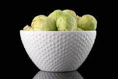 Fresh brussels sprouts. On white ceramic bowl  on black background Royalty Free Stock Photography