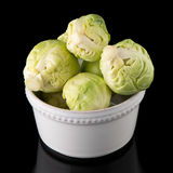 Fresh brussels sprouts. On white ceramic bowl isolated on black background Royalty Free Stock Photos
