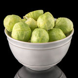 Fresh brussels sprouts. On white ceramic bowl isolated on black background Royalty Free Stock Image