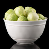 Fresh brussels sprouts. On white ceramic bowl isolated on black background Stock Photo