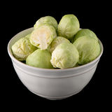 Fresh brussels sprouts. On white ceramic bowl isolated on black background Stock Images
