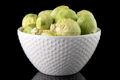 Fresh brussels sprouts. On white ceramic bowl isolated on black background Stock Photography