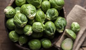 Brussels Sprouts in wooden bowl on rustic background Stock Photography