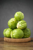 Fresh brussels sprouts on wooden table. A heap of fresh brussels sprouts on wooden table Royalty Free Stock Images