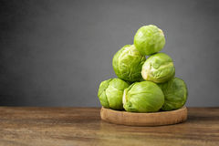 Fresh brussels sprouts on wooden table. A heap of fresh brussels sprouts on wooden table Royalty Free Stock Photo