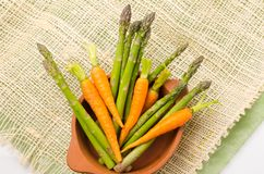 Fresh bunch of green asparagus and carrots  in. Ceramic terracota bowl on a hemp cloth Royalty Free Stock Photography