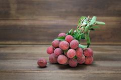 Fresh bunch of lychee fruit Litchi chinensis on wooden background. Royalty Free Stock Photography