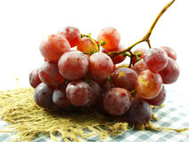 Fresh bunch of red grapes on tablecloth Royalty Free Stock Images