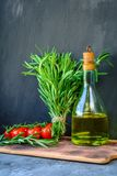 Fresh garden bunch of rosemary, tomatoes with a bottle of rosemary oil or olive oil on cutting board over stone background. Fresh bunch of rosemary, tomatoes stock photos