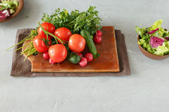 Fresh bundle of different vegetables. On a wooden board on a light surface Royalty Free Stock Photos