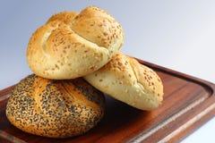 Fresh buns. Three fresh white rolls on chopping board Royalty Free Stock Photography
