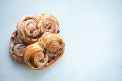 Fresh buns with raisins and icing on blue background. Top view with copy space.  Stock Photography