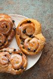 Fresh buns with raisins and icing on old rusty background. Top view.  Stock Images