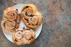 Fresh buns with raisins and icing on old rusty background. Top view with copy space.  Stock Photos