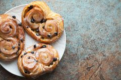 Fresh buns with raisins and icing on old rusty background. Top view with copy space.  Royalty Free Stock Images