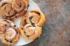 Fresh buns with raisins and icing on old rusty background. Top view with copy space.  Royalty Free Stock Image