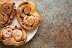 Fresh buns with raisins and icing on old rusty background. Top view with copy space.  Stock Photo
