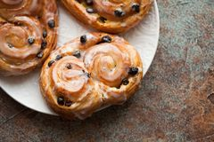 Fresh buns with raisins and icing on old rusty background. Top view with copy space stock photography