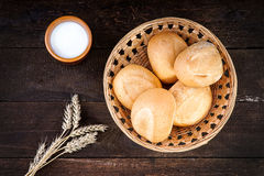 Fresh buns in wicker basket and milk cup. Fresh buns in wicker basket with milk cup Royalty Free Stock Photo