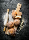 Fresh buns on a wooden cutting Board with a rolling pin and spikelets. On black rustic background stock photography