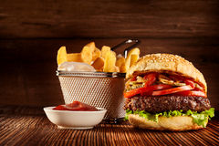 Fresh burger with basket of French fries Stock Photos