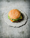 Fresh Burger with cheese and meat on a stone stand. Stock Photos
