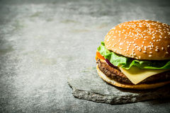 Fresh Burger with cheese and meat on a stone stand. Royalty Free Stock Photo