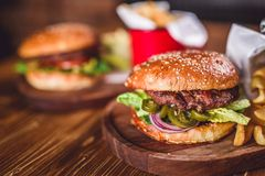 Fresh burger closeup. Fresh burger closeup on wooden table Stock Image