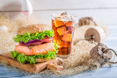 Fresh burger with fish served with cold drink Stock Images