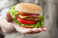 Fresh burger in the man's hand Royalty Free Stock Photos