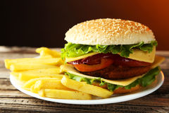 Fresh burger on plate on a brown wooden background Royalty Free Stock Images