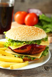 Fresh burger on plate on wooden background Stock Photography