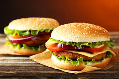 Fresh burgers on wooden background Royalty Free Stock Image