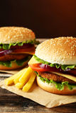 Fresh burgers on wooden background Royalty Free Stock Photos