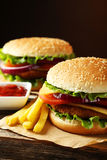 Fresh burgers on wooden background Royalty Free Stock Images