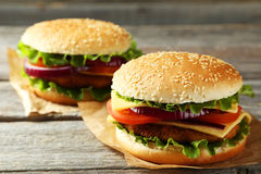 Fresh burgers on wooden background Stock Images