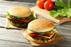Fresh burgers on wooden background Royalty Free Stock Photo