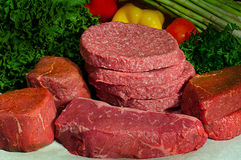 Fresh Butcher Block Raw Beef. Raw beef on butcher paper with fresh vegetables in the background.  Steaks shown are New York Strip, Fillet Mignon, Top Sirloin Royalty Free Stock Photography