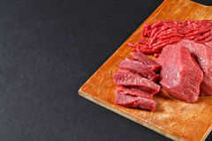Fresh butcher cut meat assortment on black background Royalty Free Stock Photography