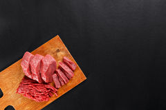 Fresh butcher cut meat assortment on black background Royalty Free Stock Photos