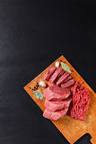 Fresh butcher cut meat assortment on black background Stock Photos