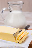 Fresh butter in a bar and a jug of milk Stock Images
