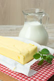 Fresh butter in a bar and a jug of milk Royalty Free Stock Photography
