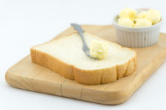 Fresh butter on bread isolated Stock Photography
